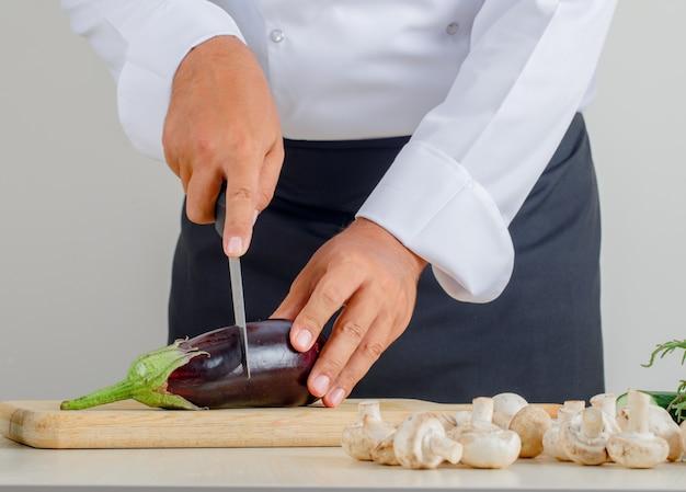 Melanzana maschio di taglio del cuoco unico sul bordo di legno in uniforme e grembiule in cucina