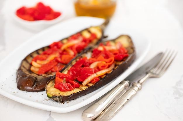 Melanzane arrostite con peperone sul piatto bianco
