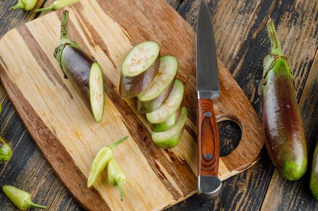 Melanzane con fette, coltello, peperoni piatti giaceva sul tagliere di legno e