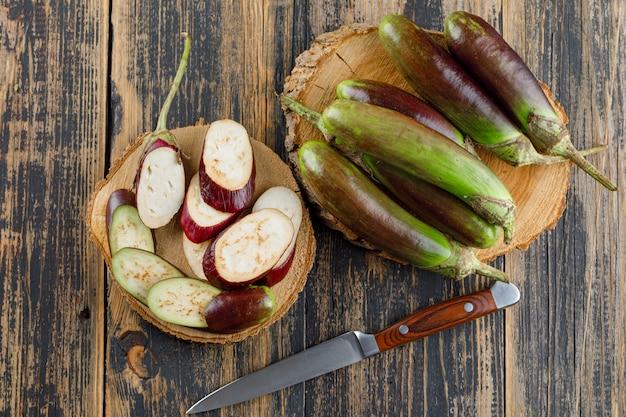 Melanzane con fette, coltello piatto giaceva su legno e taglieri