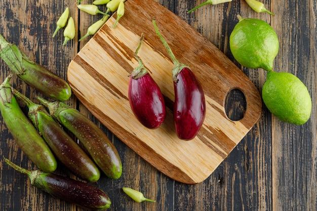 Melanzane con limoni, peperoni piatti giacevano sul tagliere di legno e