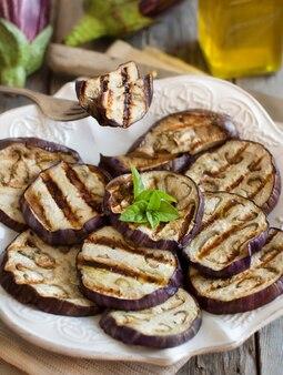 Melanzane grigliate condite con olio d'oliva sulla fine del piatto su