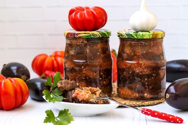 Melanzane in salsa acuta di pepe, pomodori e aglio in barattoli sul tavolo, raccolto per l'inverno, foto orizzontale