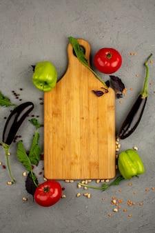 Melanzane nere una vista dall'alto di verdure fresche mature come pomodori rossi e peperoni verdi insieme a erbe verdi e scrivania marrone su un pavimento chiaro