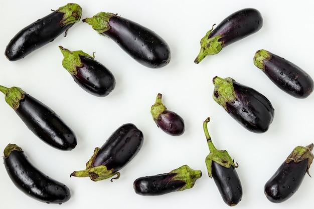 Melanzane organiche sparse su fondo bianco, concetto dell'alimento biologico, orientamento orizzontale
