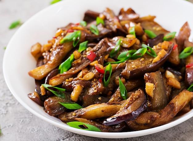 Melanzane speziate piccanti in stile coreano con cipolla verde. melanzane saltate. cibo vegano