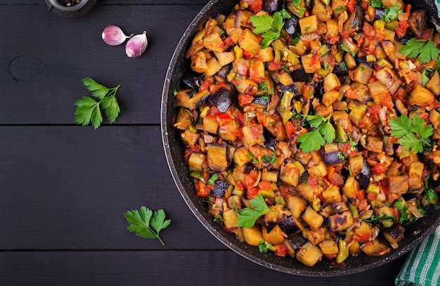 Melanzane stufate vegetariane, peperoni, cipolle, aglio e pomodori alle erbe