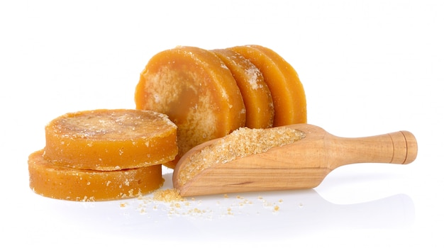 Melassa dura della canna da zucchero o jaggery e zucchero in mestolo su fondo bianco