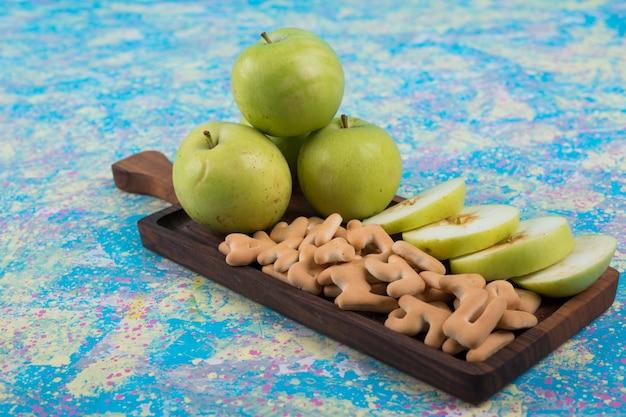 Mele a fette verdi con cracker sulla tavola di legno, angolo di visione.