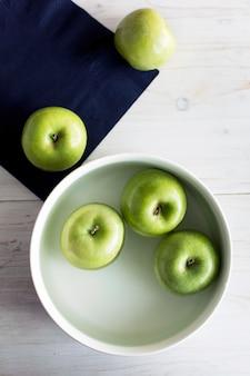 Mele di colore verde sul tavolo