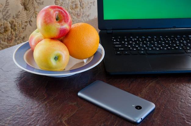Mele e arance su un piatto accanto a un computer portatile, smart phone sul tavolo. pausa salutare