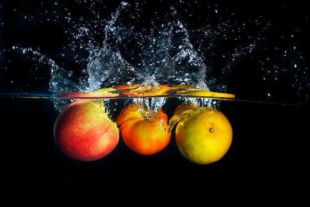 Mele e arancia che spruzza nella spruzzata blu chiara dell'acqua