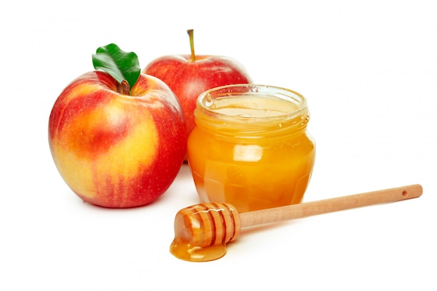 Mele e barattolo del miele per la festa ebrea del nuovo anno isolata su bianco