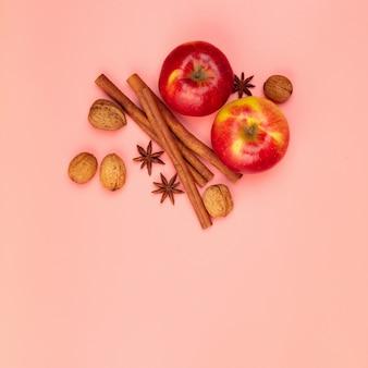 Mele e spezie sul tavolo rosa, piatto laici