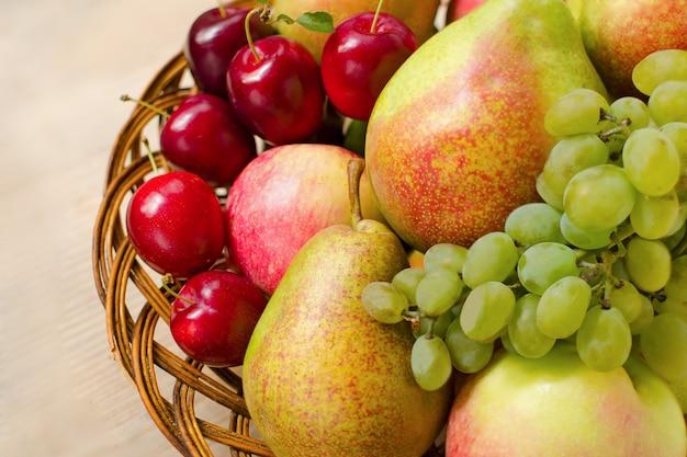 Mele fresche, pere, uva e prugne in un piatto di legno intrecciato