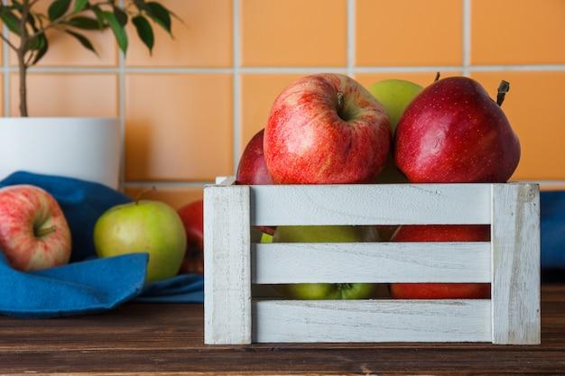 Mele in una vista laterale bianca della scatola di legno su un fondo di legno ed arancio delle mattonelle
