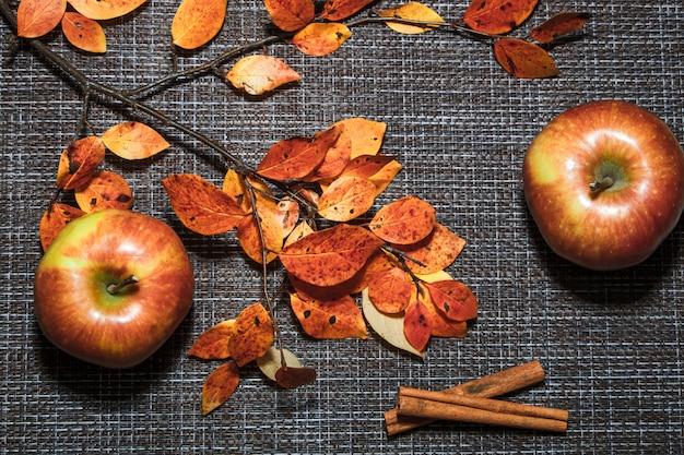Mele mature di autunno su una priorità bassa dei fogli dell'arancio