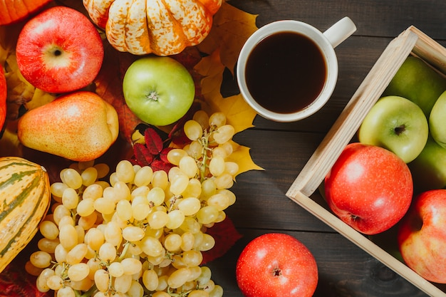 Mele mature in una scatola con zucche, mele, uva, pere e tazza di caffè su legno scuro.