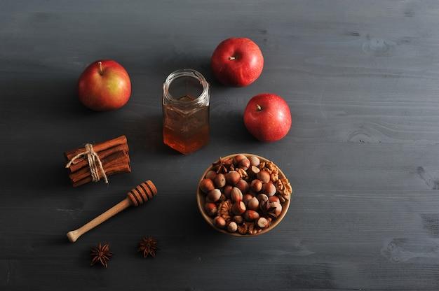 Mele, miele e noci sul tavolo scuro