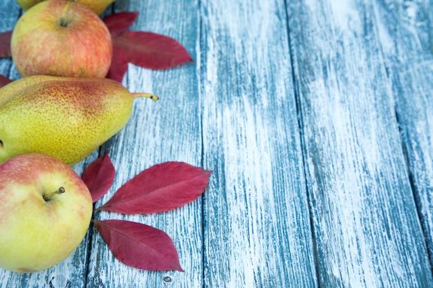 Mele, pere e foglie di autunno su fondo di legno. sfondo autunnale