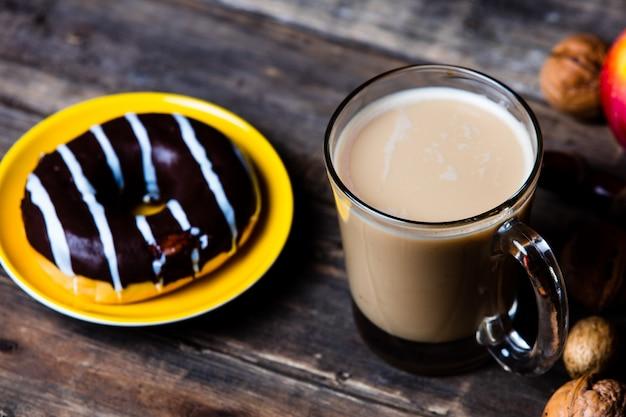 Mele, pigne, tazza di caffè, ciambella e noci