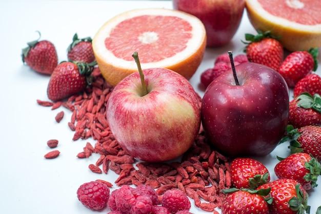 Mele rosse e altra frutta e verdure rosse su una priorità bassa bianca