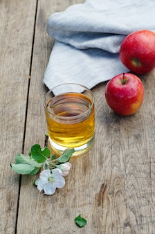 Mele rosse e gustose con un bicchiere di sidro (succo di mela) sul tavolo di legno