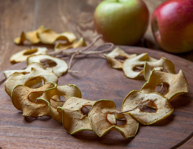 Mele secche vista laterale sul tagliere rotondo e mele fresche sulla tavola di legno