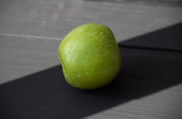 Mele succose verdi con gocce d'acqua su fondo di legno scuro.