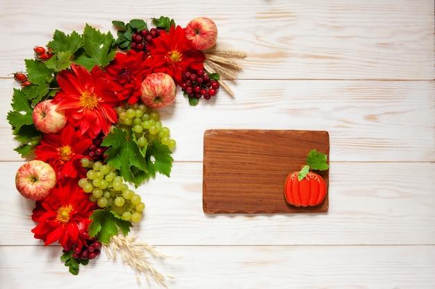 Mele, uva, fiori rossi della dalia, sorbe rosse e miele con lo spazio della copia