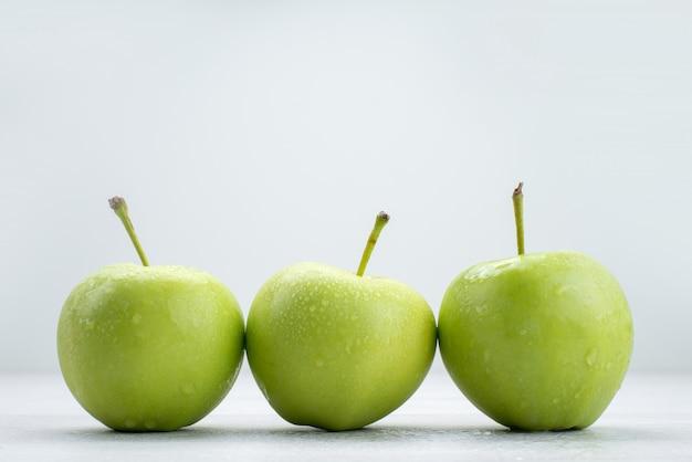 Mele verdi di vista frontale allineate sul pasto dell'alimento del succo molle della frutta bianca