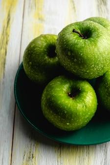 Mele verdi fresche sulla vecchia tavola di legno. cibo sano ed ecologico. armonia dei colori