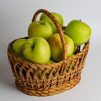 Mele verdi in un cestino su bianco. giardinaggio immagine quadrata