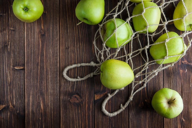 Mele verdi in una borsa netta e intorno su un fondo di legno. vista dall'alto. spazio per il testo