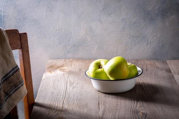 Mele verdi in una ciotola bianca su una tavola di legno vuota. il concetto di uno stile rustico.