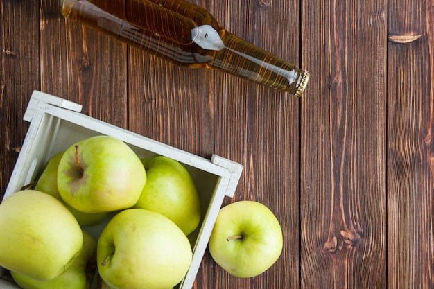 Mele verdi in una scatola di legno con la disposizione del piano del succo di mele e lo spazio di legno del fondo per testo