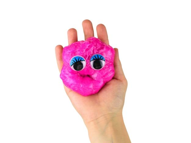 Melma rossa divertente con gli occhi in mano del bambino isolata. giocattolo antistress. giocattolo per lo sviluppo delle capacità motorie della mano.