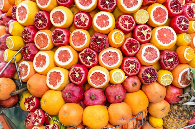 Melograni maturi e succosi, metà pelati, arance pronte per essere spremute per succo fresco.