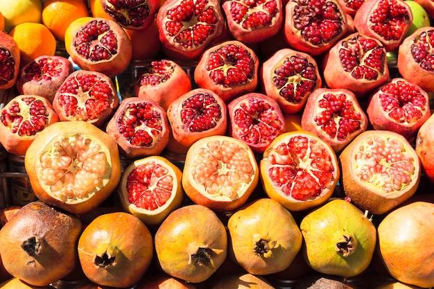Melograni maturi e succosi pelati a metà pronti per essere spremuti per il succo fresco.