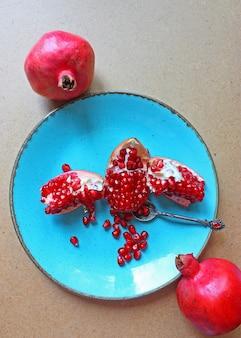 Melograni rossi interi e tagliati dentro e fuori il piatto