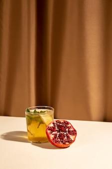 Melograno diviso in due con la bevanda deliziosa del cocktail sistemata sullo scrittorio contro la tenda marrone
