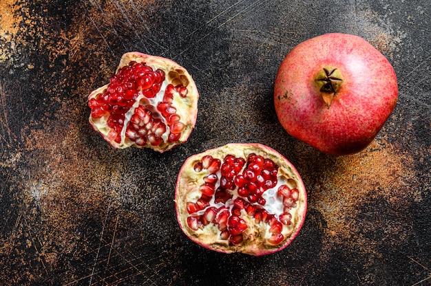 Melograno maturo frutta biologica. sfondo nero. vista dall'alto