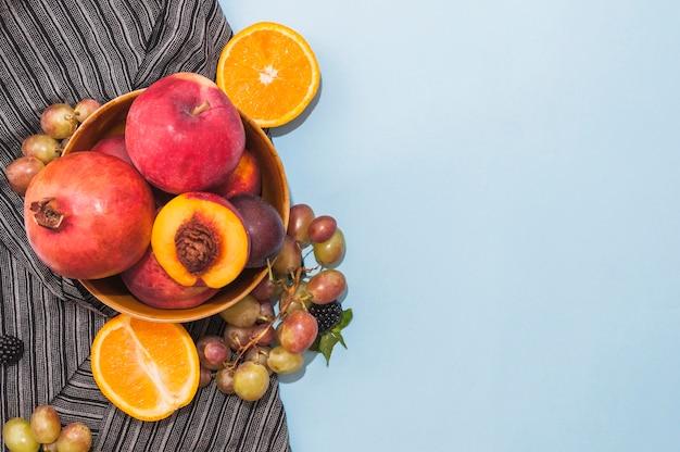 Melograno; mela; pesca; uva e agrumi divisi a metà su fondo blu
