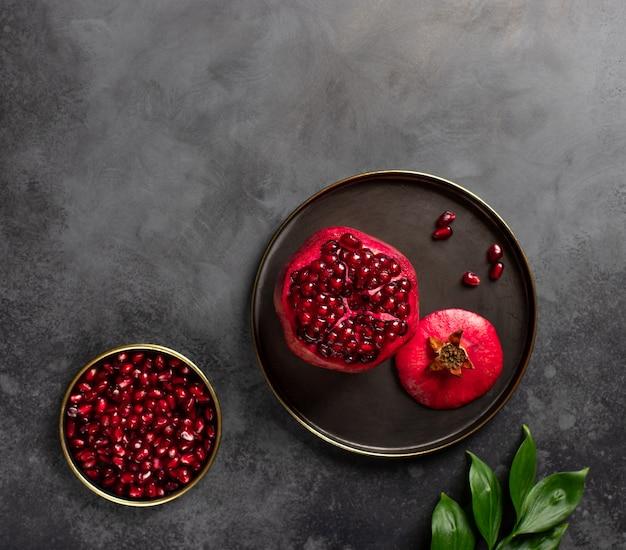 Melograno organico maturo per una superficie scura dell'alimento sano