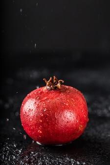 Melograno rosso del succo sulla tavola scura. melograno utile