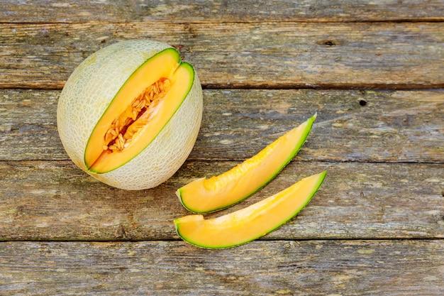 Melone affettato giallo sulla tavola di legno