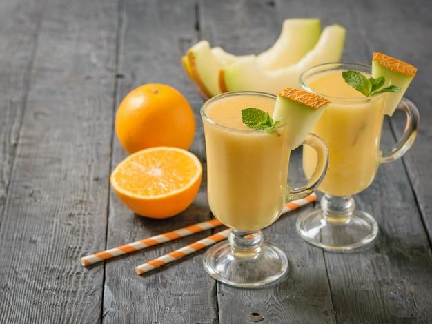 Melone, arancia, tubi da cocktail e frullati di melone in bicchieri di vetro su un tavolo rustico.