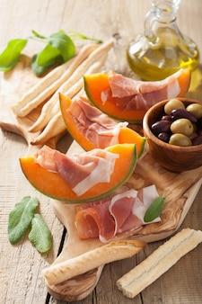 Melone cantalupo con olive di prosciutto grissini. antipasto italiano
