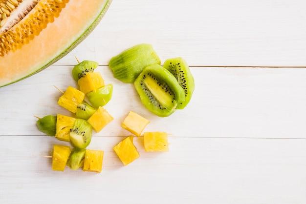 Melone diviso in due con fette di kiwi e ananas su piano in legno
