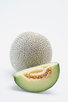 Melone fresco del cantalupo di hami con le fette isolate su fondo bianco.